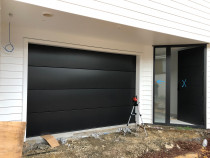 Smooth flat panel .95 in ebony by Hibiscus Garage Doors Ltd - New door on a new house.