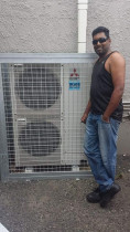 Airconditioning being repaired. - This unit being repaired after a hot day struggle.