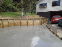 Parau jobsite - this job involved excavation of around 80cubic mtrs of spoil.we then built a new timber retaining wall and finished the job of with 100mm thick steel reinforced light broom finished for grip coloured grey concrete.this not only gave the client room to back around but plenty of extra parking for visitors and also for the teenagers to park