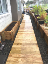 Boardwalk footpath over ornamental riverstone with garden boxes