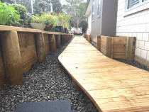 Boardwalk footpath over ornamental riverstone retaining wall and garden boxes