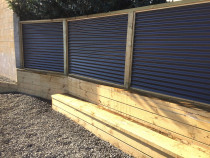 Horizontal colour steel fence over small retaining wall and wooden seat