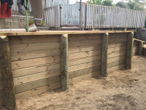 Retaining walls using tongue and groove timber to create separate flat sections levels