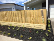 Vertical fence using 88 x 18mm dressed timber over small retaining wall. Garden surrounded by black mulch
