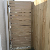 Pedestrian gate with horizontal dressed timber cladding over aluminium frame gate with vertical paling fence