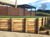 Retaining walls terracing a steep bank with instant lawn and garden layers with trellis fencing