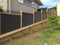 Retaining wall on steep slope with horizontal colour steel fence