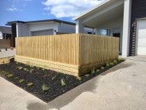 Vertical fence using 88 x 18mm dressed timber over small retaining wall. Garden cover is black mulch
