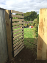 Pedestrian gate with wide gap horizontal dressed timber cladding over aluminium frame gate with vertical paling fence