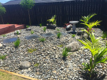 Ornamental riverstone garden with birdbath and deck