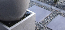 Water feature paving stone walkway and grey ornamental riverstone