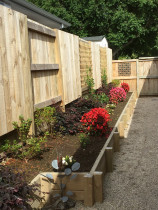 Raised offset gardens and good neighbour fencing with pea-sand walkway