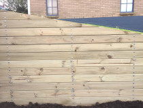 Retaining wall with exterior cladding and heavy duty landscape screws