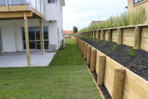 Raised garden with black mulch two tiers retaining walls and instant lawn