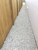 Inset paling fence with white riverstone pathway