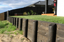 Retaining wall using rough sawn timber painted black with instant lawn and deck