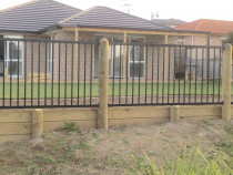Aluminium security fencing with rounded timber posts over a retaining wall and instant lawns