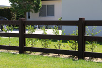 Painted post and rail fence on lifestyle block