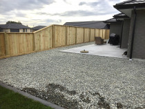 Paling fence inset between posts face side with ornamental riverstone ground cover