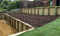 Retaining walls using tongue and groove timber with nugget bark orchard area and instant lawn