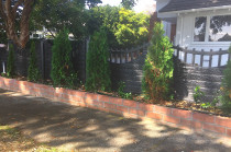 Brick raised garden built outside existing boundary fence.
