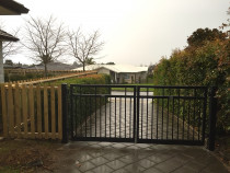 Driveway aluminium gate pair joining dressed timber picket fence.