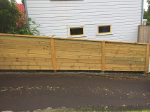 Tongue and groove solid timber fencing following ground contour
