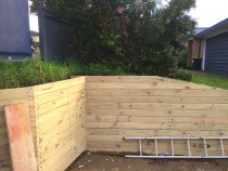 Retaining wall with external cladding and landscaping screws