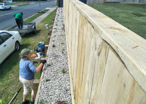 Retaining wall fence and raised garden with ornamental riverstone
