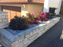 Raised garden in shingle with white ornamental riverstone