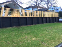 Open Picket Fence using dressed timber on top of a retaining wall.