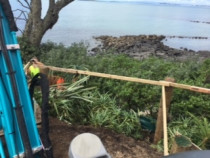 Drilling holes on the cliff face in Takapuna, putting poles in for a bacony - AJLC Excavation