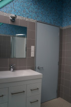 Artistic bathroom - Cleanline Bathrooms Ltd - Mosaic wall and floor tiles, interesting wall light