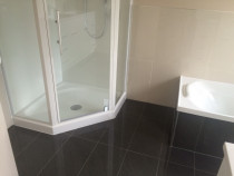 Handy Home Solutions - Separate shower and bath with dark floor tiles and cream wall tiles