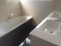 Handy Home Solutions - Double vanity with dark floor and bath front tiles.