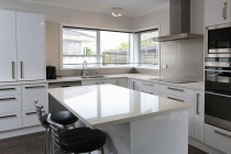 Jag Kitchens - A modern kitchen design with crisp white stone benchtops exudes functionality and comfort.You can read about this kitchen makeover here - https://www.jagkitchens.co.nz/new-life-for-outdated-kitchen/