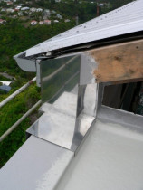 Stainless steel flashing by Buildstrong - Triangular window was leaking where it met the trafficgard deck and roof and wall cladding.  Fitted custom stainless steel flashing.