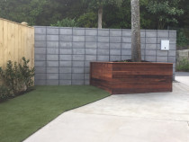 Contrast - Sculptaview Landscaping Ltd - Artificial Turf, Kwila timber planter. Block wall that has been honed, Stained, sealed with a DPS and then sealed with a gloss finnish. Hedge planted.